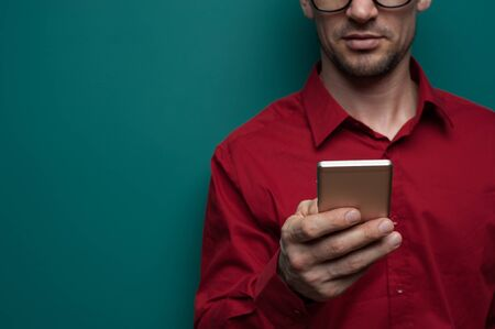 Close-up - Portrait of a positive young man in glasses and a red shirt holding a smartphone in his hands on a green background. Advertising concept and place for text