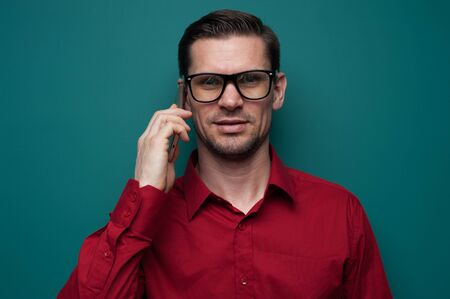 Portrait of a positive young man in glasses with phone Stock Photo - 131933059