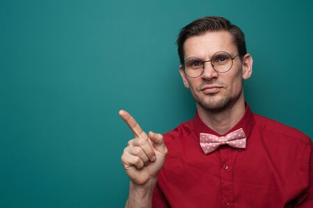 Portrait of a cute young man showing finger on a green background Stock Photo