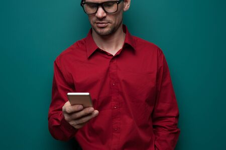 Portrait of a positive young man in glasses with phone Stock Photo - 132387439