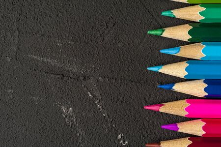 Close-up of multicolored sharpened pencils lie on each other on the table of an artist or a child. The concept of creativity and drawing Stock Photo - 132391730