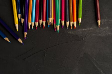 Close-up of bright sharpened pencils lie on the colors of the rainbow on a black background side by side. The concept of childrens creativity and preparation for school. Copyspace Stock Photo