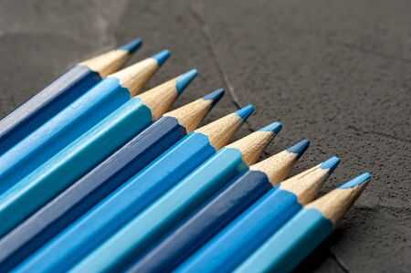 Close-up bright sharpened pencils of blue and gray shades lie on a black countertop. The concept of creativity of artists and children. Copyspace