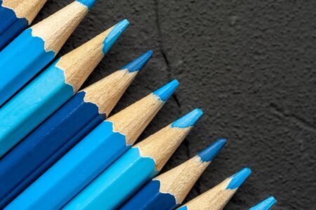 Close-up bright sharpened pencils of blue and gray shades lie on a black countertop. The concept of creativity of artists and children. Copyspace Stock Photo - 132397169