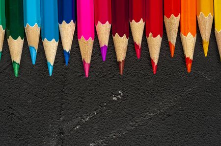 Close-up of multicolored sharpened pencils lie on each other on the table of an artist or a child. The concept of creativity and drawing Stock Photo