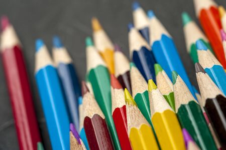 Close-up of colored sharpened pencils lie on each other on the table of an artist or a child. The concept of creativity and drawing Stock Photo
