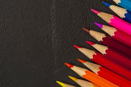 Close-up of multicolored sharpened pencils lie on each other on the table of an artist or a child. The concept of creativity and drawing Stock Photo - 132398413