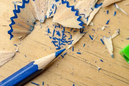 Close-up of a bright blue pencil just sharpened with a sharpener lying next to the chips on the table. The concept of drawing and creativity of children Stock Photo
