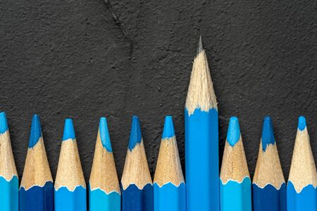Close-up of a blue pencil lies slightly higher than blue pencils on a black background. The concept of distinctness from others. Copyspace