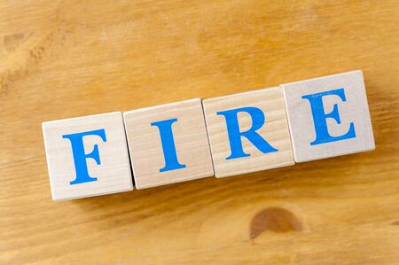 Wooden cubes with word FIRE on table.