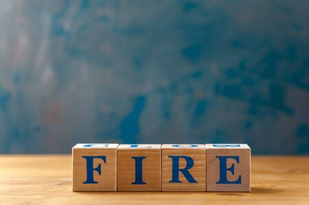 Wooden cubes with word FIRE on blue table.