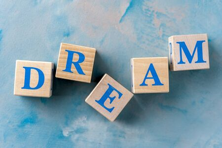 Wooden cubes with word DREAM on blue table.