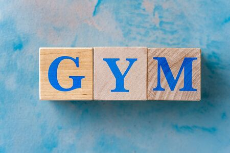 Wooden cubes with word GYM on blue table. Stock Photo