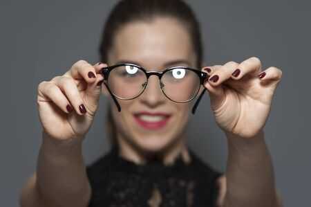 Young positive blurred woman holding glasses Stock Photo