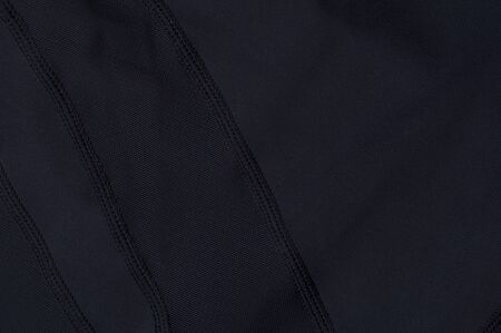 Close-up fragment of black nylon garment. The concept of quality clothing. Place for advertising. Advertising concept