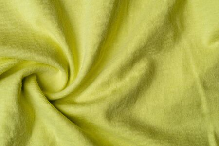 Close-up fragment of crumpled beautiful yellow cotton fabric. Concept of high-quality raw materials for tailoring casual clothes. Advertising space Stock Photo