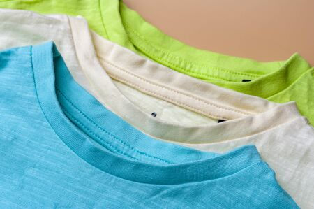 Closeup three knitted t-shirts lying on each other in a store or in a closet at home. Concept of comfortable and quality casual wear. Comfortable clothes concept Stock Photo