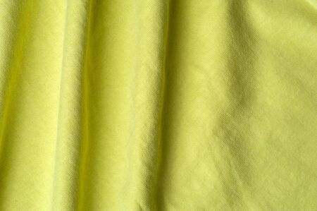 Close-up fragment of a beautiful yellow cotton fabric. Concept of high-quality raw materials for tailoring casual clothes. Advertising space Stock Photo