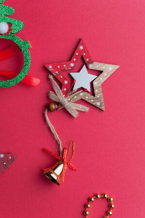 Christmas Wooden Stars, Handbells And Golden Beads on Red Background.