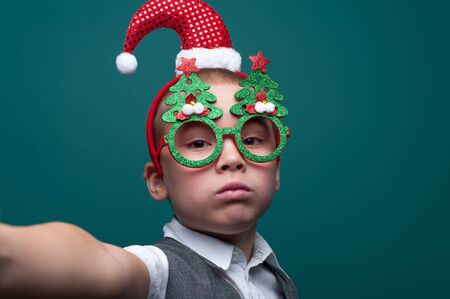 Serious little boy wearing headband with Santa Claus Hat posing on green wall. 写真素材 - 134356684