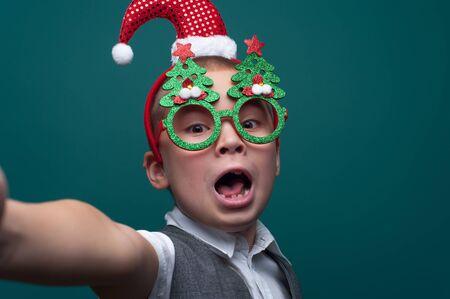 Adorable little boy in Christmas accessories making selfie 写真素材