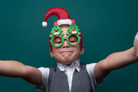 Adorable little boy in Christmas accessories making selfie 写真素材 - 134356939