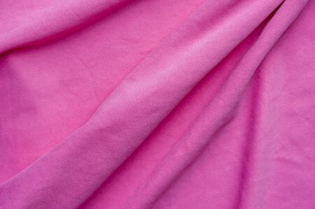 Closeup fragment of crumpled pink polyester fabric 写真素材