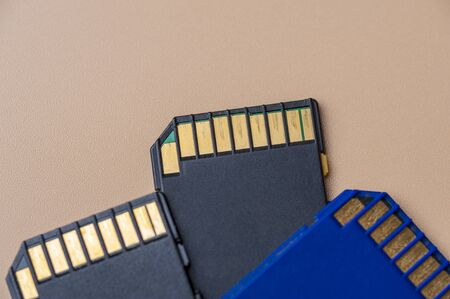 Close-up three memory cards lie on a beige table