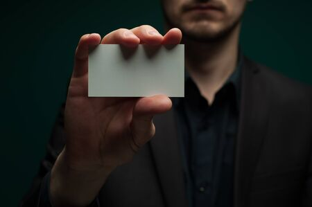 Man holds a blank white business card 写真素材