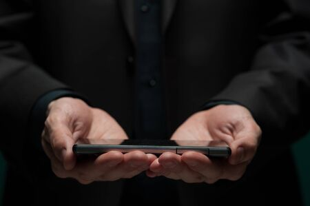 Man holds a smartphone and typing a message 写真素材