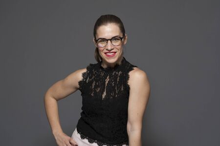 Smiling beautiful young woman in glasses posing on a gray background