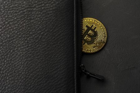 Close-up of a gold-plated Bitcoin coin in a wallet. The concept of salary and personal savings in modern currency. Concept of finance and economics. Copyspace Reklamní fotografie