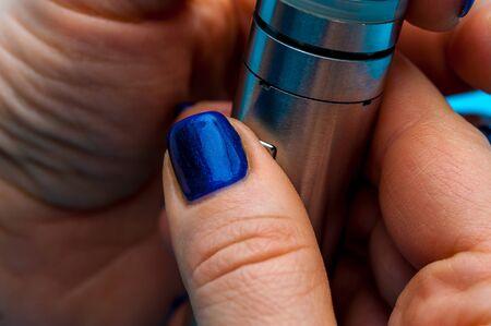 Close-up - female hands preparing device to vaping e-cigarette. 写真素材