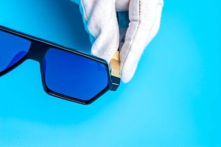 Hands in gloves are holding designer sunglasses Stock Photo - 135777406