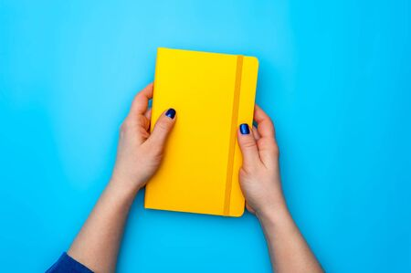 Beautiful female hands lie on a yellow diary Stock Photo - 135777414