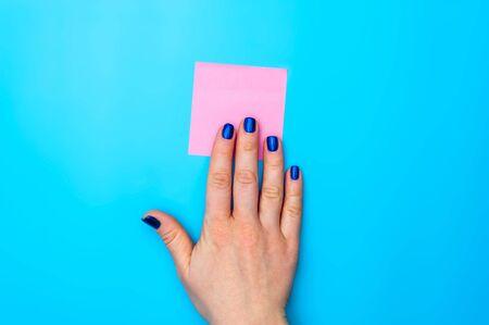 Female hand lying on pink reminder sheet Stock Photo - 135777416