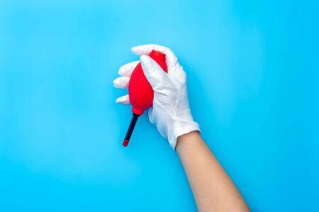 Top view female hand wearing white gloves cleaning up with air dust blower. Stock Photo - 135777418