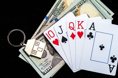 Close-up keychain in the form of house lies in it a pile of dollar bills and playing cards lying on a black surface. 写真素材