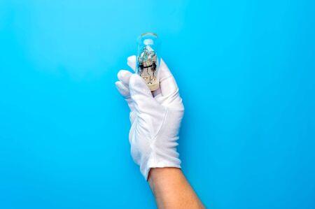 Hands in white gloves carefully hold light bulb