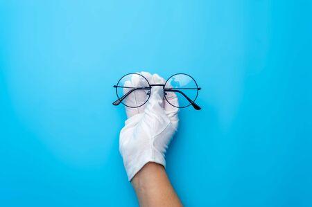 Hands in gloves are holding designer sunglasses Stock Photo - 135777419
