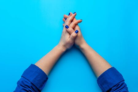 Female hand with dark blue nails showing gesture