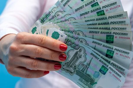 Hands of an unidentified woman with ruble banknotes 写真素材