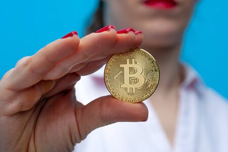 Young unidentified woman holding a bitcoin coin 写真素材