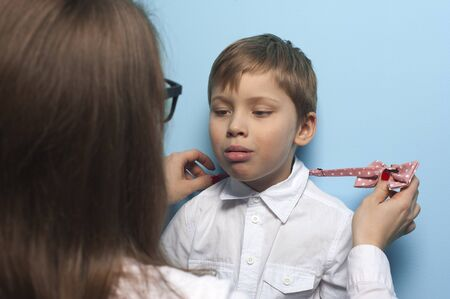 Mom puts her son a bow tie on a white shirt Stock Photo - 135777421