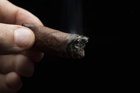 Close-up male hand holds a steaming cigar on a black background. The concept of expensive cigars and luxury gift. Advertising space Stock Photo - 135777444