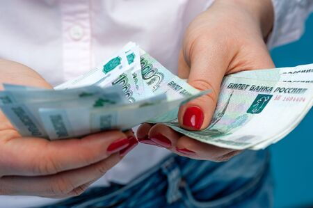 Hands of an unidentified woman with ruble banknotes Stock Photo - 136106539
