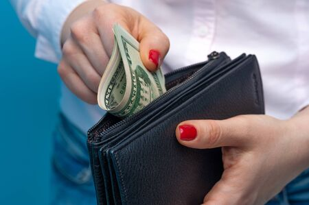 Unidentified woman's hands put rolled paper banknotes in a purse on a blue background. Funds and bank savings account Stock Photo - 136106906