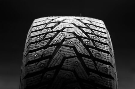 Close-up of a car tire standing upright against a black background. Automotive industry concept. The concept of sports equipment in the gym. Copyspace Stock Photo - 136107169