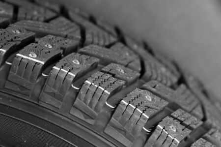 Close-up side view of a fragment of a car studded tire. Automotive industry concept. The concept of seasonal tire updates. Truck repair concept Stock Photo - 136108370