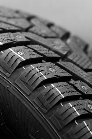 Close-up side view of a fragment of a car studded tire. Automotive industry concept. The concept of seasonal tire updates. Truck repair concept Stock Photo - 136108278